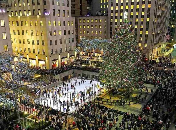 scenic overview of the hustle and bustle of the holidays at night beneath the magnificent tree in Rockefeller Center.